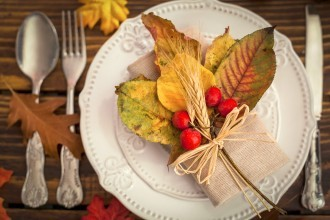 Photo of a placement setting on a table with a spoon, fork and knife and a plate with a festive fall leaves and berries decoration on it.