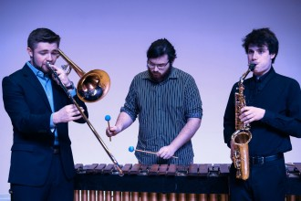WMU students William Ford playing a trombone, Evan Leffert playing a xylophone and Andrew Keating playing a saxophone.