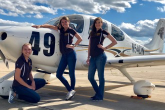 Photo of WMU aviation students Lauren Quandt, Shelby Satkowiak and Kelly Erdmann standing in front of a plane.