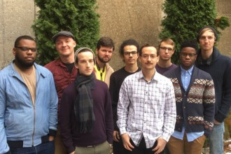 Photo of nine members of the Western Michigan University Advanced Jazz Ensemble standing in front of a wall with greenery behind them.