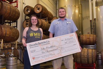 Student Ellie Maddelein with Arcadia brewer Colt Dykstra holding an oversized check for $2,000 and standing in front of brewery barrels.