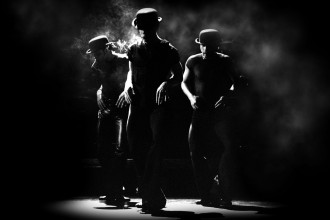 Black and white photo of three tap dancers wearing hats and simulating smoking on stage.