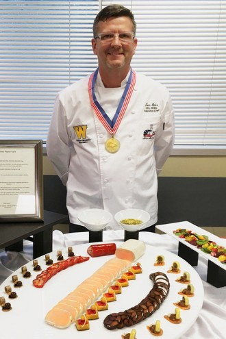 Photo of Chef Tom Giles standing in front of a platter of his award-winning food.