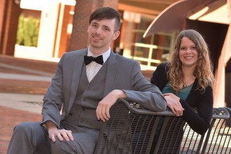 Avery Green and Desi Taylor sitting on a bench outside Schneider Hall, home of the WMU Haworth College of Business.