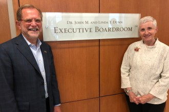 Photo of Dr. John and Linda Dunn in front of a sign that reads Dr. John M. and Linda T. Dunn Executive Board Room.