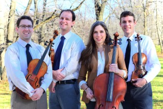 Photo of four members of the Kontras Quartet holding their instruments and standing in front of trees.