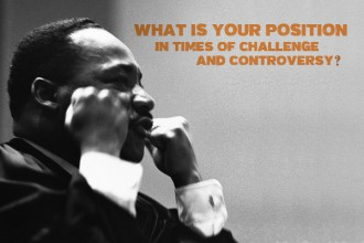 Photo of Dr. Martin Luther King Jr. with both of his arms raised and his fists clentched and the words What is your position in times of challenge and controversy?