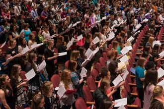 Dozens of high school students sing in Miller Auditiorium.