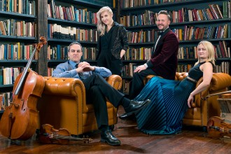 Four musicians of the Spektral Quartet sitting in chairs in front of rows of bookcases.