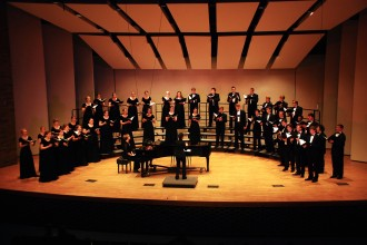 Members of WMU choirs perform on a stage in a semicircle, facing conductor.