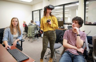 Students sitting at computers and wearing virtual reality gear and controls in a VR lab at Waldo Library.