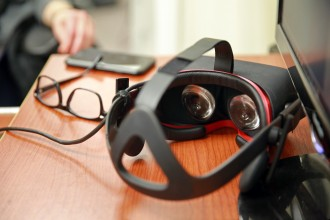 Photo of close up of virtual reality goggles, glasses and a computer.