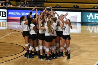 Photo of the WMU volleyball team cheering in a circle on a gym floor.