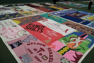 Photo of a large quilt spread on the ground with artwork and names honoring victims of AIDS.