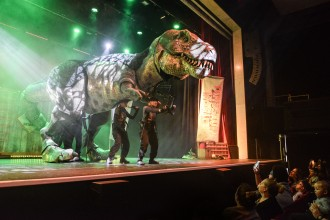 Photo of two actors on a stage with a large Dinosaur prop and people looking on from the floor.