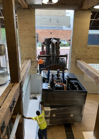 Photo of a machine being loaded into the window of the manufacutirng laboratory.