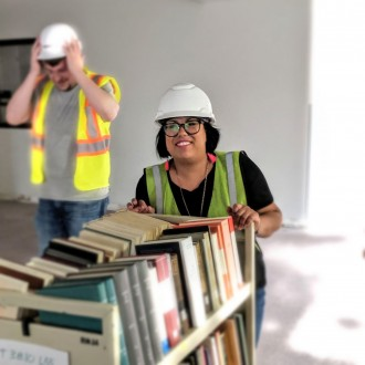 Photo of librarian Juliana Espinosa moving a cart of books with a man standing behind her.