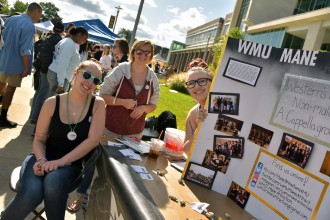 Photo of members of WMU's Mane Attraction registered student organization at a table with an informational poster.