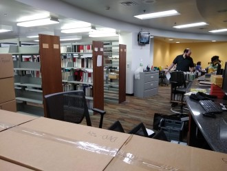 Photo of employees moving boxes back onto shelves in the renovated service desk area of Waldo Library.