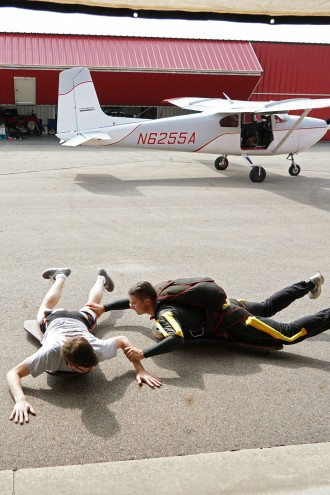 Two members of the Skydive Broncos practice their form on the pavement in front of an airplane.