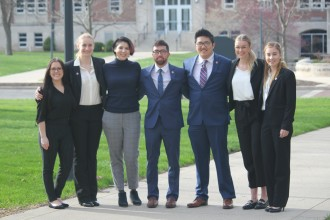 Photo of seven WMU marketing students standing outside sholder-to-shoulder.