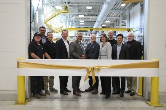 Photo of WMU President Edward Montgomery, WMU Pilot Plants staff and paper industry representatives standing in front of a gold ribbon inside the facility.