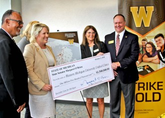 WMU and a state official pose with a ceremonial check for the Unified Clinics.