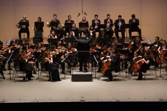 University Symphony Orchestra performing on Miller Auditorium's stage with conductors hands straight up in the air