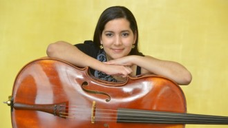 cellist allyson perez posing with her cello
