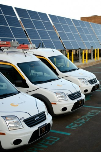 vans parked in front of an array of solar panels