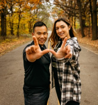 "two students face the camera and collectively create a ""W"" with their hands"