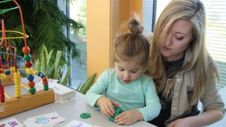 Photo of a student in the Autism Center of Excellence helping a child learn.