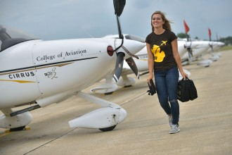 Photo of a WMU flight student walking in front of a row of the University's Cirrus planes.