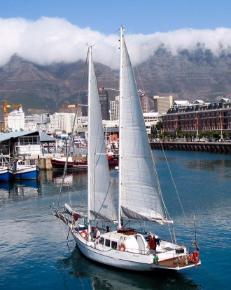 Photo of the Cape Town waterfront. In the foreground is a large sailboat that is about to dock.