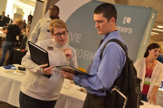Photo of a young man at one of WMU's previous career-related events discussing his career prospects with a female representative from an employer participating in the event.