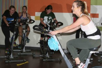 Photo of an instructor on a stationary exercise bike with class members, also on these bikes, shown in the background.