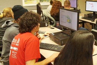 Photo of several groups of students gathered around computers as they work out geographic information science problems during an in-class GIS Challenge contest.