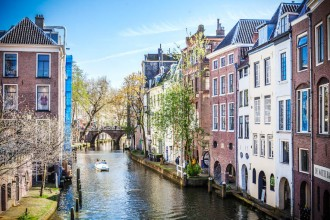 Photo of a long canal in Utrecht, the Netherlands, flanked on both sides by four-story buildings.