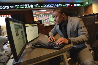 Photo of a student working at a Bloomberg terminal in the business college's Greenleaf Trust Trading Room.