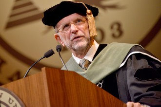 Photo of WMU President John M. Dunn, dressed in academic regalia, speaking at a commencement ceremony.