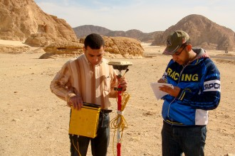 Photo of Abdelmohsen taking notes while a colleague takes readings from a scientific instrument. The two are working in a flat area of light-colored sand that recedes into a series of darker brown and reddish hills.