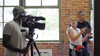 Dr. Jennifer Machiorlatti on location in an aging brick building and giving directions to two students during a video session.