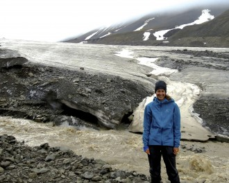 Photo of McNeal standing on the rock-strewn fringe of a melting glacier with a stream of rushing water swirling at her feet.