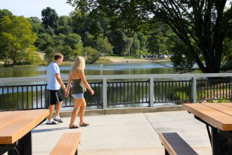 Photo of two students strolling across the scenic Goldsworth Valley Pond walkway.