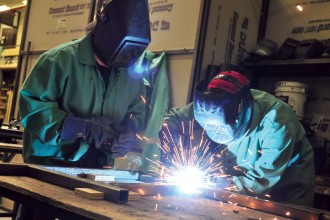 Photo of two students welding materials in the theatre department's scene shop.