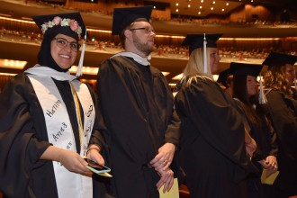 Photo of a line of five students, dressed in academic regalia, at a commencement ceremony.