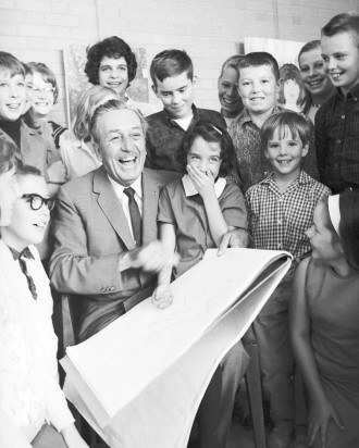 A black-and-white photo of a seated Walt Disney surrounded by children. On his lap, Disney is holding a large tablet of paper.