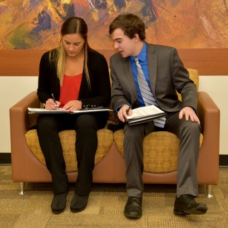 Photo of two students talking to one another as they jot down notes during a career fair.