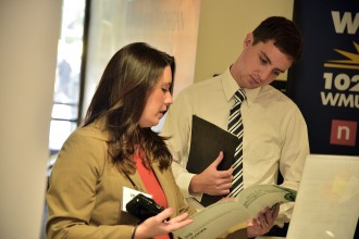 A female corporate representative discusses job opportunities with a male student attending a WMU career fair.