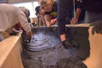 Concrete canoe team members lean over a Styrofoam mold and trowel on concrete.